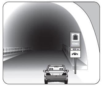 Şekildeki gibi yeterince aydınlatılmamış tünele giriş yapan aracın sürücüsü, aşağıdakilerden hangisini yapmak zorundadır?